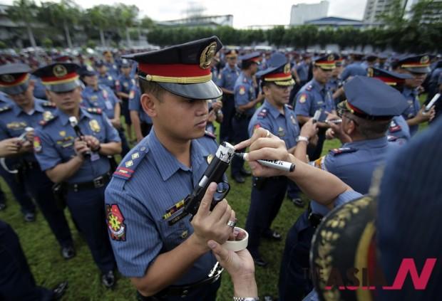 필리핀 경찰이 새해 총기 무사고를 기원하는 글귀를 새기고 있는 모습