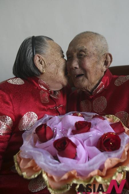 발렌타인데이, 중국 산둥성 지난의 한 마을에서 93세된 할아버지 유시양바오(오른쪽)가 자신과 결혼한지 74년된 부인에게 장미를 선사하고 입맞춤을 받고 있다.