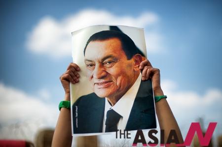 이집트 카이로에서 호스니 무바라크 전 대통령 지지자가 그의 사진을 들고 있다.