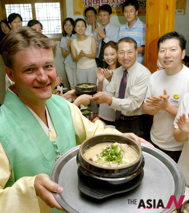 서울 토속촌에서 외국인이 삼계탕을 들고 포즈를 취하고 있다. 삼계탕은 맛 뿐만 아니라 건강에도 좋은 최고의 보양식이다.