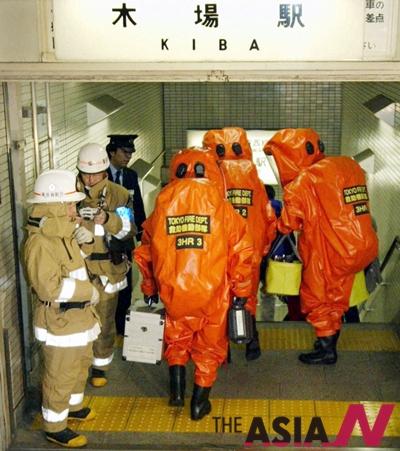 보호복을 입은 일본 소방관들이 2004년 12월 화학물질로 추정되는 액체로 오염된 전철 차량이 있는 도쿄의 한 지하철역으로 들어가고 있다. 관계자들은 여성 1명이 화상을 입고 다른 2명이 부상을 입었다고 밝혔다. 경찰은 아직 액체의 정확한 성분은 밝혀지지 않았으나 강한 알칼리성이라고 전했다.