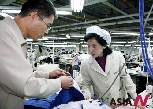 2007년 개성공단 입주 기업으로 첫 생산 공장을 추가 준공하는 신원의 개성공단 입주공장의 북한 근로자들이 생산품에 관한 이야기를 나누는 모습