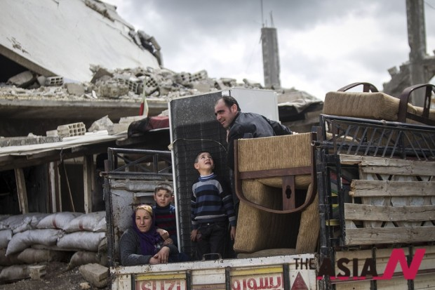 시리아 쿠르드족 난민 가족이 폐허가 된 시리아 코바니를 망연자실한 표정으로 쳐다보고 있다.