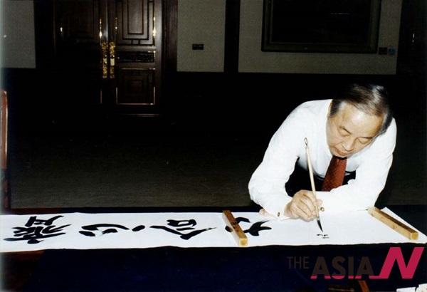 1998년 김영삼 대통령이 신년휘호로 제심합력(齊心合力)을 쓰고 있는 모습.