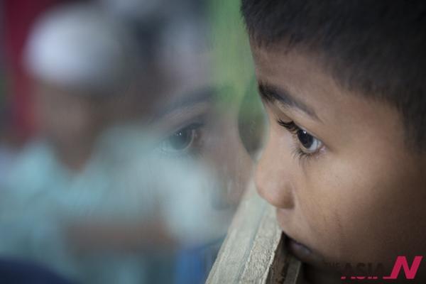 로힝야족 출신의 한 아이가 창 밖을 내다보고 있다.