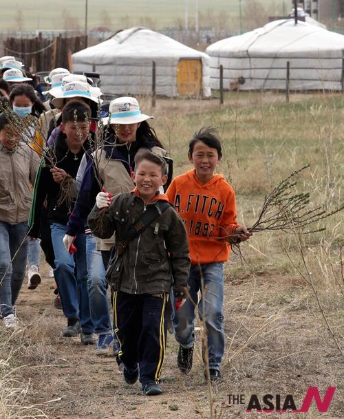 대한항공 신입직원들과 몽골 어린이들이 몽골 울란바토르 사막에서 묘목을 들고 나무를 심기위해 이동하고 있다.