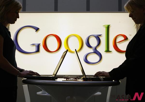 조명이 들어온 구글 로고 밑에서 사람들이 노트북으로 작업을 하고 있다.