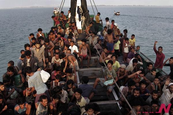 해양난민들이 작은 배에서 현지 어민들의 구조를 기다리고 있다.