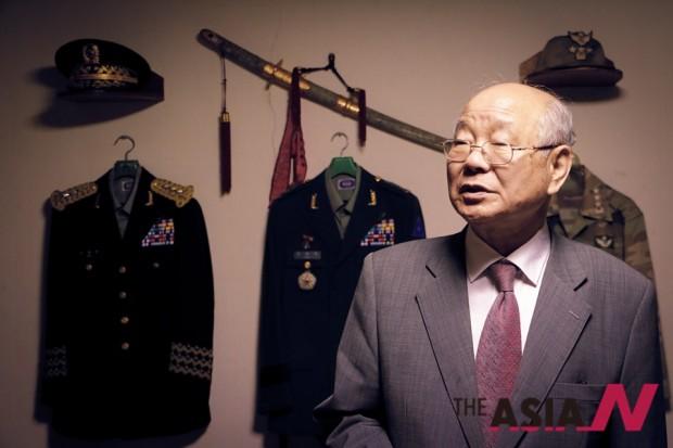 민병돈 장군이 현역 중장 시절 입었던 예복, 정복, 전투복 및 삼정도와 군모를 배경으로 당시를 회상하고 있다.
