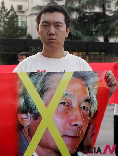 한 중국 청년이 17일 베이징주재 일본 대사관 앞에서 고이즈미 준이치로 일본 총리의 대형 사진 위에 X표를 그린 대형 배너를 들고 고이즈미의 야스쿠니 신사 참배에 항의하는 시위를 벌이고 있다.