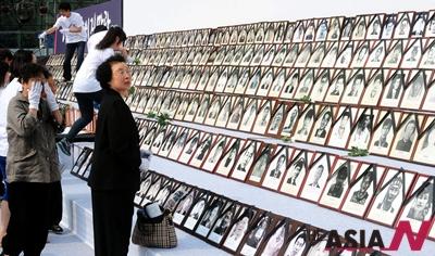 2012년 6월10일 오후 서울광장에서 열린 '6월 항쟁 25주년 국민행사, 21회 민족민주열사·희생자범국민추모제'에서 참석자들이 도우미들의 도움을 받아 헌화를 하고 있다.