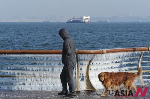 중국 다롄시 해안가에서 한 시민이 산책하고 있다.