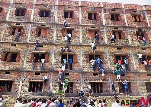 지난 18일(현지시간) 고교 입학 자격시험이 치러진 인도 동부 비하르주 하지푸르의 한 고사장 밖에서는 학부모들이 '커닝 페이퍼'를 전하기 5층 고사장 건물의 벽을 타고 오르는 모습.