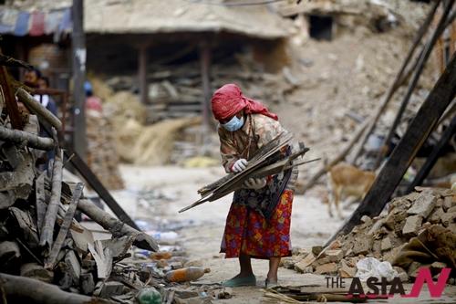 네팔 여성이 랄릿푸르 지진 잔해 속에서 쓸 만한 물건을 챙기고 있다.