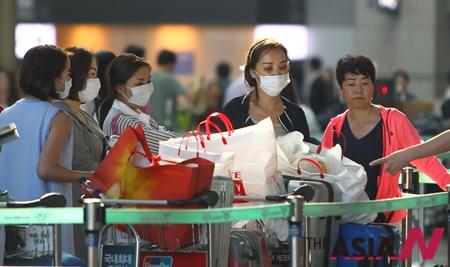 마스크를 쓴 중국 관광객이 인천공항에서 탑승 수속을 위해 대기하고 있는 모습.