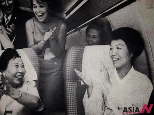 50년 전 미국행 보잉707 기내에서 아리랑을 부르는 육영수 여사. 존슨 대통령이 가난한 한국의 대통령 부부에게 보내준 전용기여서 주변에 미국인들이 보인다.