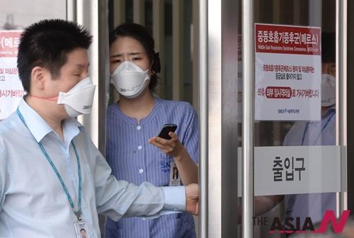 중동호흡기증후군(메르스) 환자가 결국 사망에 이르고 3차 감염 환자까지 발생하는 등 연일 환자가 늘고 있는 가운데 메르스 감염자 격리센터가 설치되어 있는 2일 서울 연건동 서울대학교병원 응급실 앞에 병원관계자들이 마스크를 하고 업무를 보고 있다.