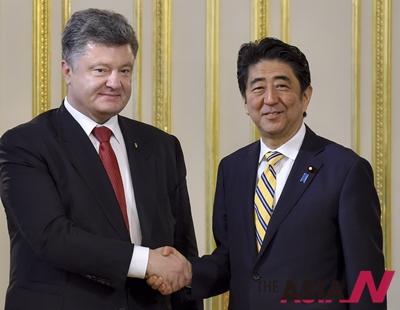 우크라이나 페트로 포로셴코 대통령(왼쪽)과 일본 신조 아베 총리(오른쪽)이 지난6일 열린 일본-우크라이나 정상회담에서 악수를 하고 있다.