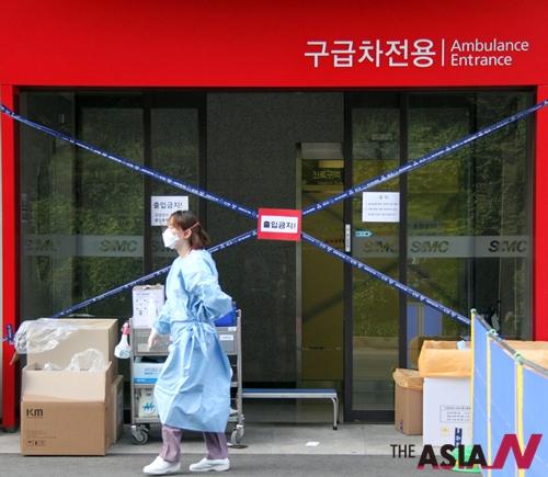 서울의 한 병원에 근무하는 의료진이 병원 옆을 걸어가고 있다. 이 병원에서는 7명의 환자가 메르스에 감염됐다.