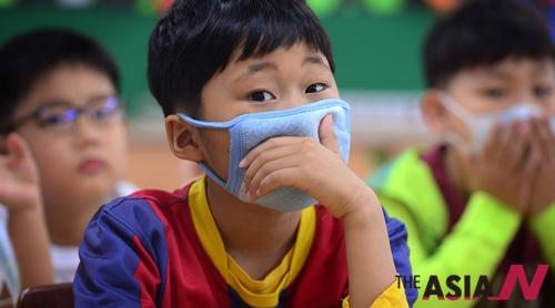 국내 메르스(MERS·중동호흡기증후군) 환자가운데 10대 확진자가 처음으로 발생한 8일 오전 서울 미근동 미동초등학교에서 발열체크를 마친 학생들이 마스크를 만지고 있다.
