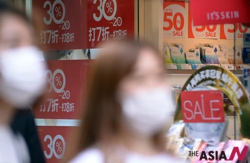 명동상가에 붙은 세일표지판 앞을 마스크를 한 관광객들이 지나고 있다.