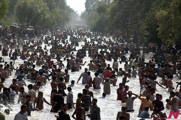 파키스탄 시민이 21일(현지시간) 동부 라호르에서 폭염에 운하에서 더위를 피하고 있다.