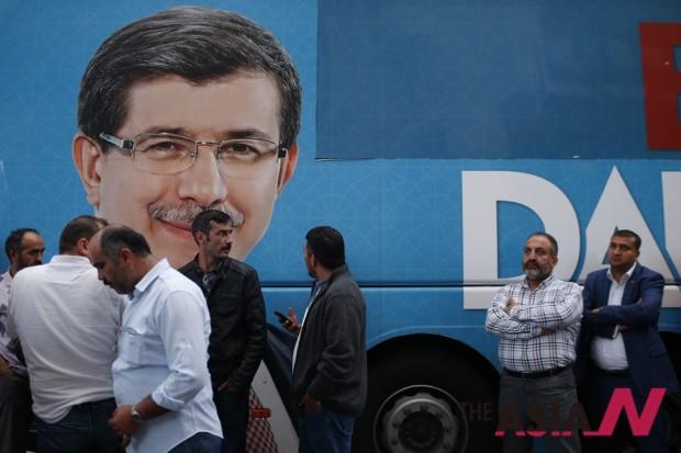 6월7일 이스탄불에서 AKP 지지자들이 아흐멧 다부토울루 APK당 대표 겸 총리의 포스터 옆에서 선거결과를 지켜보고 있다.