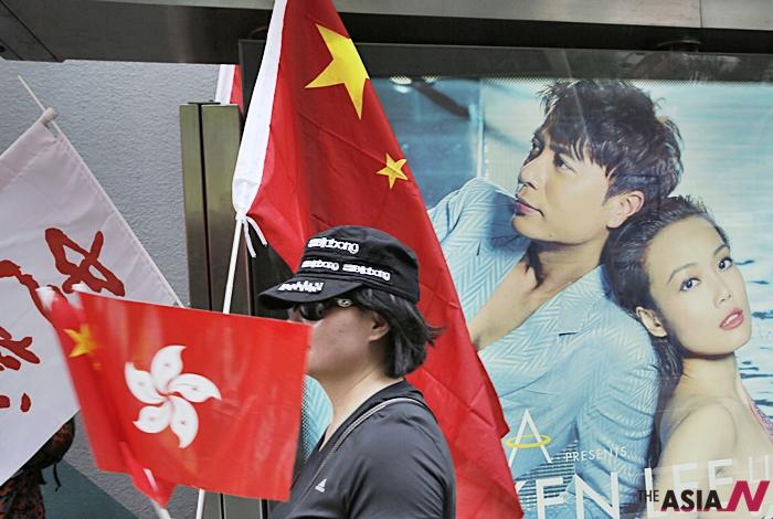 '홍콩 반환' 18주년을 맞아 친중국 시위자가 홍콩과 중국 국기를 들고 거리행진에 나서고 있다.