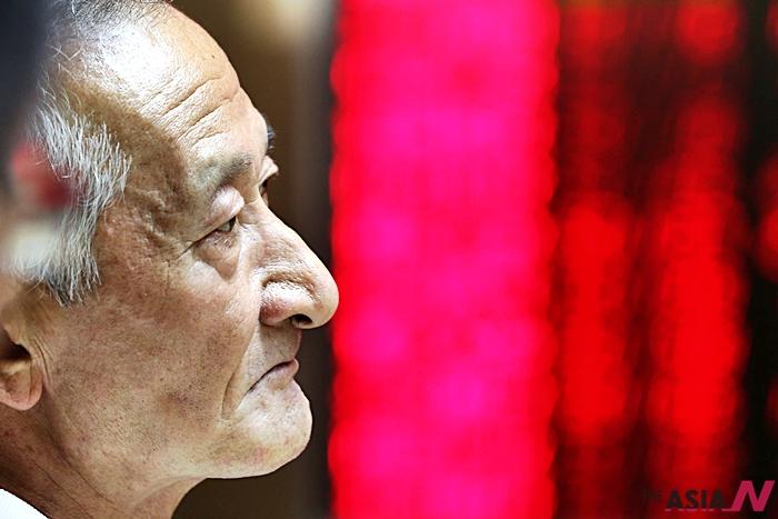 6일 베이징의 한 증권거래소에서 전광판 앞에서 한 투자자가 수심에 찬 표정을 짓고 있다.
