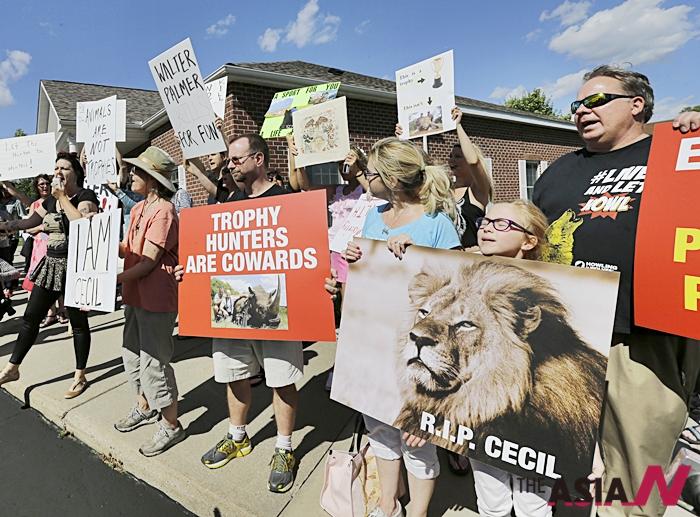 짐바브웨에서 사자 '세실'을 잔혹하게 사냥한 미국 치과의사 제임스 파머의 사무실 앞에서 시민들이 야생동물 밀렵반대 시위를 벌이고 있다.