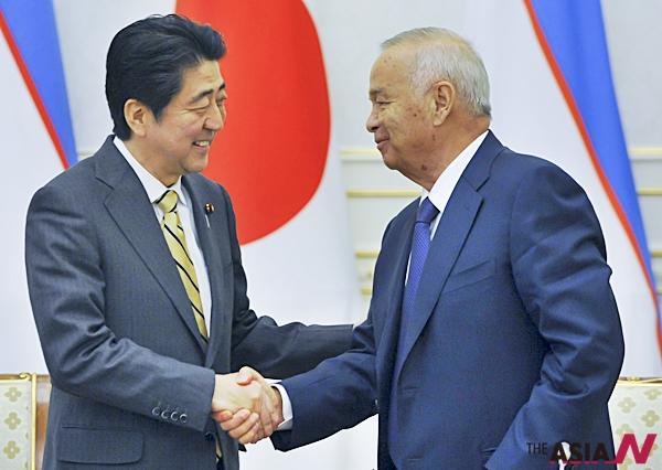 지난 25일 일본 신조 아베 총리가 우즈베키스탄 이슬람 카리모브 대통령과 악수를 나누고 있다.