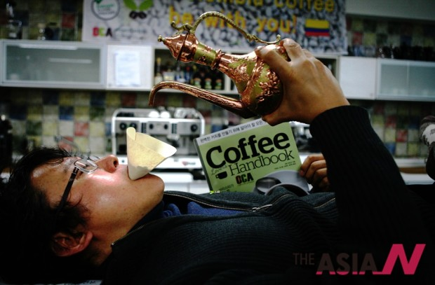 필자가 질이 좋지 않은 커피의 향미를 숨기고 속이려는 '농간'을 거부하자는 의미로 바로 커피를 바로 입으로 추출하는 퍼포먼스를 보이고 있다.