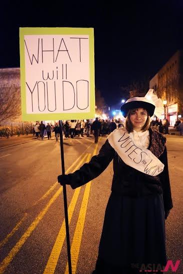 """UNCG 학생 Laura Melrose는 AiOP의 참가자로써 1911년에 미국에서 일어난 트라이앵글 화재 사건을 기반으로 두어 그 시대의 여성 시위자처럼 변장하였다. 그녀는 """"What will you do"""" 라는 간판을 들어 지나가는 사람들이 과거부터 지금까지 여성 인권이 어떠한 변화를 겪었는지 생각하게 만드는 깊이 있는 작품이었다."""