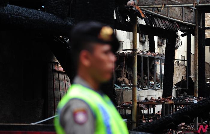 인도네시아 자카르타에서 한 경찰관은 전소한 절 앞을 지키고 서 있는 모습