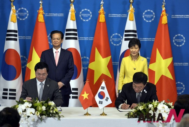 2014년 12월 박근혜 대통령과 응웬 떤 중 베트남 총리가 부산 해운대구 벡스코 인근 한 호텔에 마련된 공동기자회견장에서 한-베트남 FTA 서명을 지켜보고 있다.