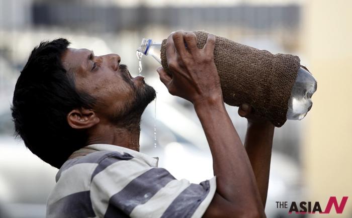 극심한 폭염으로 물병을 통째로 들이키고 있는 한 남성