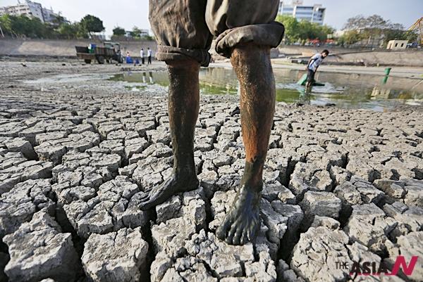 지난 24일 한 인도 남성이 가뭄으로 말라버린 아마다바드의 한 호수에 서있다.