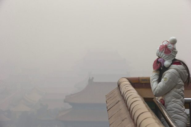 A woman adjusts her mask during a heavily polluted day in Beijing Tuesday, Dec. 22, 2015. The Chinese capital is expected to end its four-day long smog red alert on Tuesday. (AP Photo/Ng Han Guan)